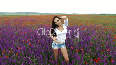Attractive young woman in blossoming field