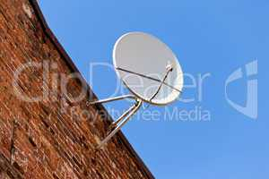 Satellite Dish mounted on old brick wall.