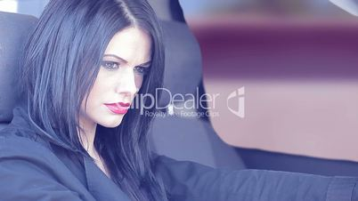 Single woman with long black hair in driver's seat of car.