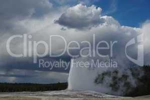Old Faithful Geysir merging with clouds, Yellowstone National Park, Wyoming