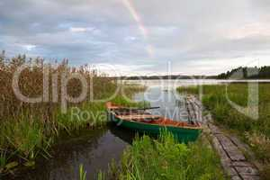 Summer's lake scenery with wooden boat and rainbow