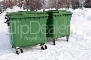 Two green recycling containers in winter park
