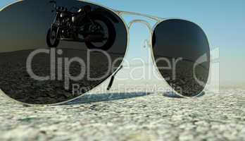glasses lying on the   asphalt  with the reflection of  the motorcycle  deformed by the heat