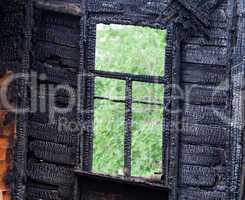 Burned wooden window frame with view to a green trees