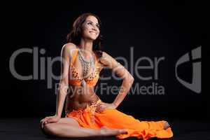 Smiling oriental dancer in orange costume