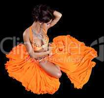 Sexy oriental dancer in orange costume
