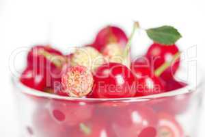 glass cup with cherries and wild strawberries on a white backgro