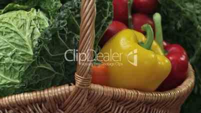 Abwärtskranfahrt auf einen Gemüsekorb mit Tomaten, Paprika, Möhrchen und Kohl.