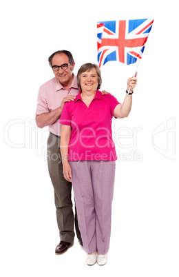 Old couple waving UK flag. Supporting nation