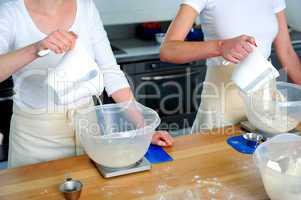 Females hand pouring water into flour bowl
