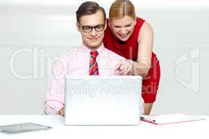 Lady pointing at something funny in laptop