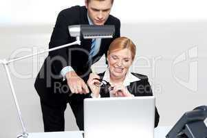 Man pointing finger at laptop screen