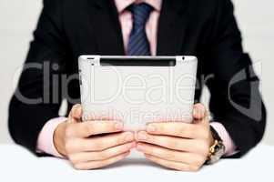 Businessman's hands holding portable device