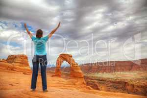 Woman with raised hands in front of Delicate Arch