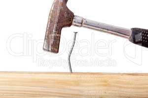 Crooked nail in the wooden board with a hammer