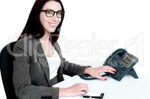 Attractive female executive dialing clients number