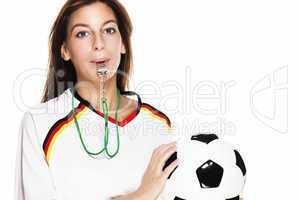 junge frau mit trillerpfeife hält fussball