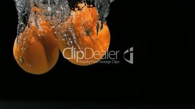 Orangen fallen ins Wasser in Zeitlupe