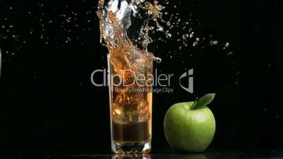 Apple juice splashing in super slow motion because of ice cube