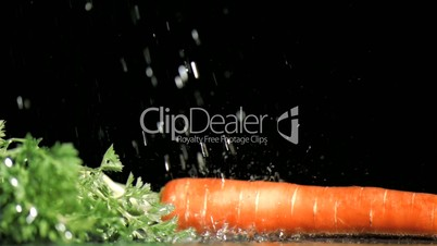 Drops of water in super slow motion falling on a carrot