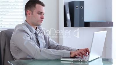 Well-dressed man typing on a laptop