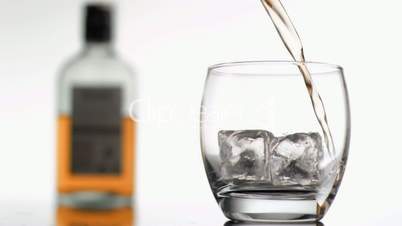 Whiskey in super slow motion filling a tumbler