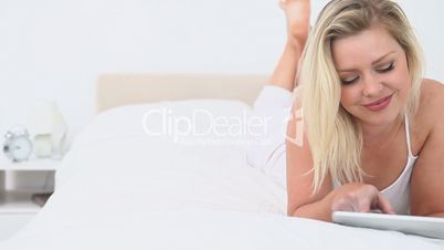 Blonde woman using an ebook while she is lying down
