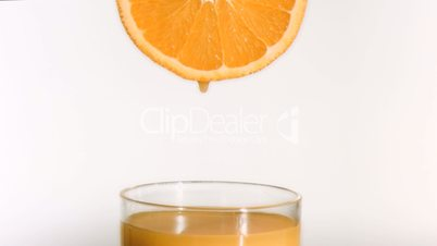 Drops of orange juice in super slow motion falling in a glass