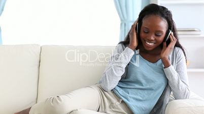 Smiling woman listening to music on a sofa