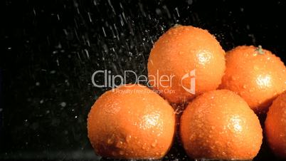 Water in super slow motion falling on oranges