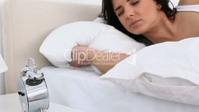 Woman looking at an alarm clock