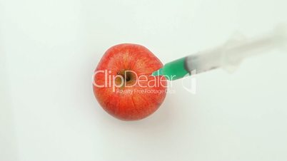 Syringe injecting a toxic product in an apple