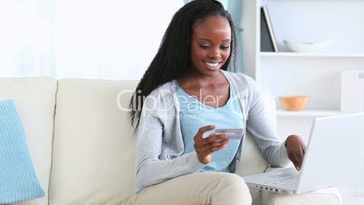 Woman holding a credit card while typing on a laptop