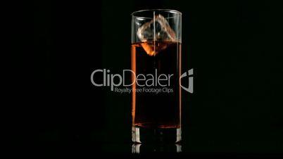 Ice cube falling in super slow motion in apple juice