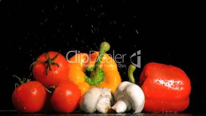 Water drops falling in super slow motion on vegetables