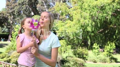 Girl and a woman blowing on a pinwheel