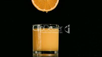 Drop falling in super slow motion from an orange slice in a full glass