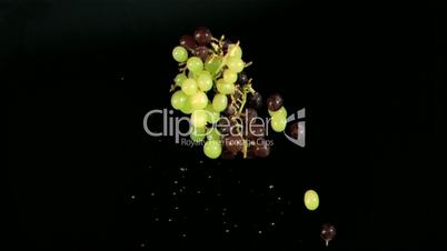 Red and green grapes falling in super slow motion
