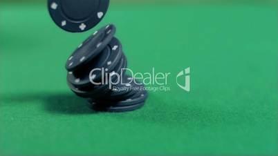 Black gambling chips falling in super slow motion