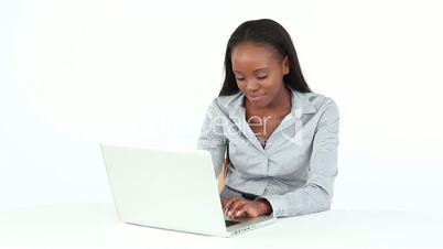 Woman typing on a computer while sitting at a desk