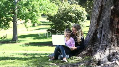 Mother and her daughter reading a book in a park