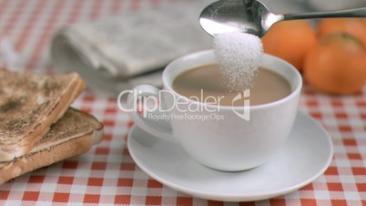 Sugar poured in super slow motion into white coffee