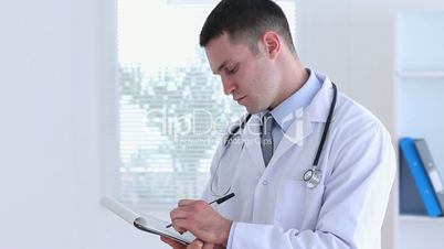 Young doctor writing on a clipboard