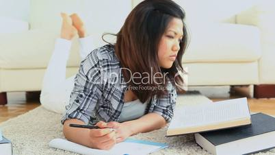 Student studying while lying on the flloor