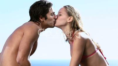 Couple kissing next to a swimming pool