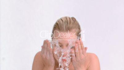 Blonde woman in slow motion splashing her face