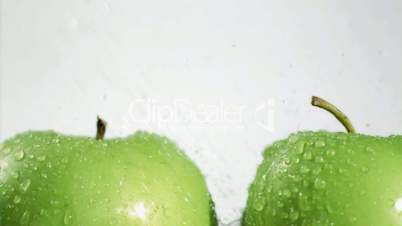Water being sprayed in super slow motion on apples