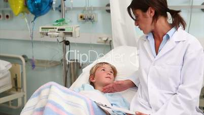 Child lying on a bed next to a doctor
