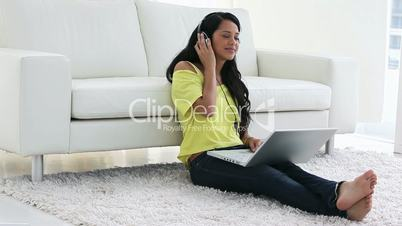 Woman listening music while using a laptop