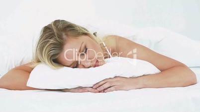 Blonde woman moving while she sleeps